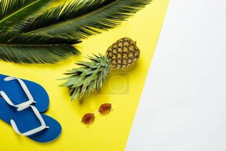 Photo pour Vue du dessus des feuilles de palmier vert, ananas, lunettes de soleil et tongs bleues sur fond blanc et jaune - image libre de droit