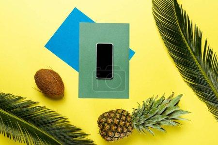 Photo pour Vue du dessus des feuilles de palmier vert, smartphone, noix de coco, ananas sur fond coloré - image libre de droit