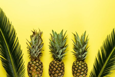 top view of green palm leaves and ripe pineapples on yellow background