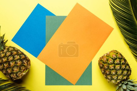 Photo for Top view of green palm leaves and ripe pineapples on colorful background - Royalty Free Image