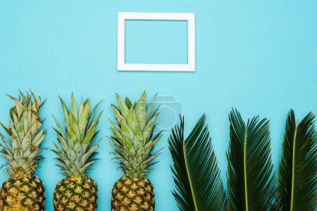 top view of green palm leaves and ripe pineapples near square empty frame on blue background