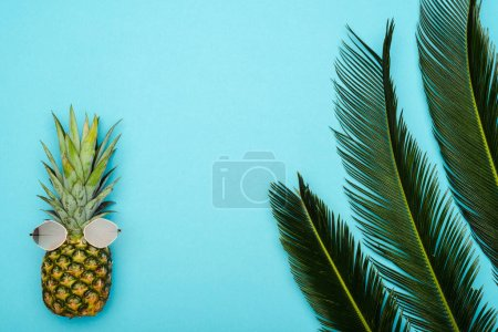 Photo for Top view of green palm leaves and ripe pineapple with sunglasses on blue background - Royalty Free Image