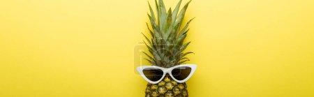 vue du dessus de l'ananas mûr dans les lunettes de soleil sur fond jaune, panoramique