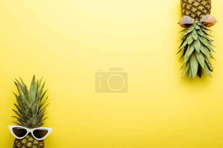 Photo for Top view of ripe pineapples in sunglasses on yellow background - Royalty Free Image