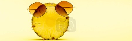delicious sweet cut pineapple in sunglasses on yellow background, panoramic shot
