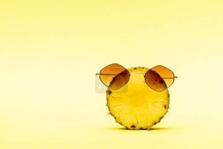 Photo pour Délicieux ananas doux coupé dans des lunettes de soleil sur fond jaune - image libre de droit