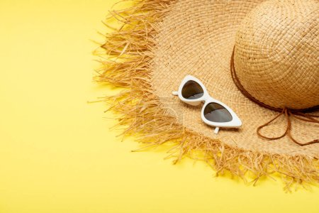 straw hat and stylish suglasses on yellow background