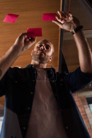Photo pour Vue à angle bas de bel homme d'affaires regardant la note collante - image libre de droit