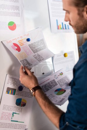 selective focus of charts and graphs in hand of businessman