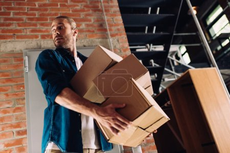 low angle view of man holding carton boxes while moving in new office