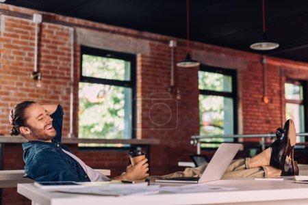 Selektiver Fokus des gut gelaunten Geschäftsmannes mit Pappbecher und Blick auf Laptop im Büro