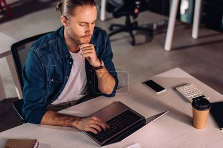 Photo for Pensive businessman using laptop near smartphone with blank screen and paper cup - Royalty Free Image