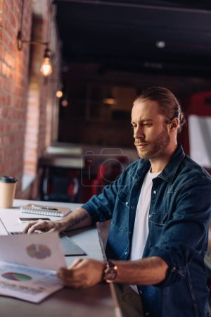 Photo for Selective focus of bearded businessman looking at charts and graphs near laptop in office - Royalty Free Image