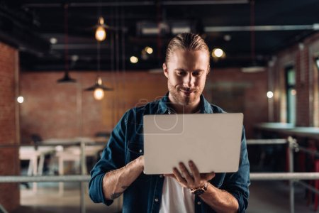 bearded businessman holding and using laptop in modern office