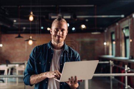 Photo pour Homme d'affaires souriant tenant et utilisant un ordinateur portable dans le bureau moderne - image libre de droit