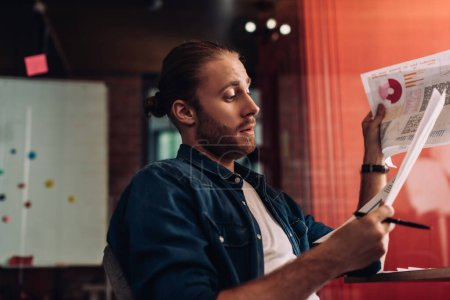 Photo for Selective focus of bearded businessman looking at charts and graphs - Royalty Free Image