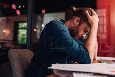 enfoque selectivo del empresario molesto sentado en el escritorio en la oficina