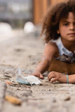 Photo for Selective focus of poor african american kid reaching dirty medical mask near curly sister - Royalty Free Image