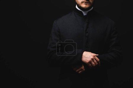 Photo pour Vue recadrée du prêtre isolé sur noir - image libre de droit
