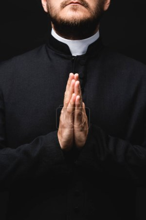 Photo for Cropped view of priest with praying hands isolated on black - Royalty Free Image