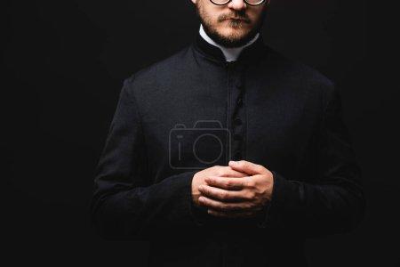Photo pour Vue recadrée du prêtre avec les mains serrées isolées sur noir - image libre de droit