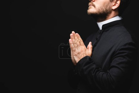 cropped view of bearded priest with praying hands isolated on black
