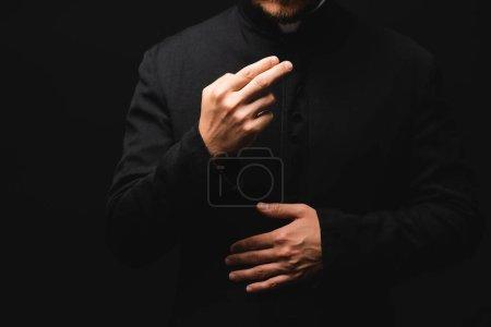 Photo pour Vue recadrée de prêtre gesticulant tout en priant isolé sur noir - image libre de droit