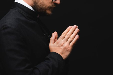 Photo for Partial view of priest with praying hands isolated on black - Royalty Free Image
