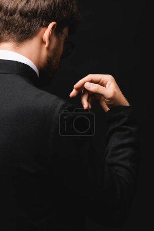 Photo pour Vue partielle du geste du prêtre isolé sur noir - image libre de droit