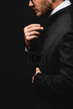 Photo pour Vue latérale du prêtre gesticulant et priant isolé sur noir - image libre de droit