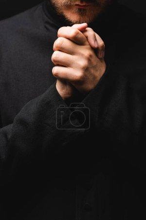 Photo pour Vue recadrée du prêtre avec les mains serrées priant isolé sur noir - image libre de droit