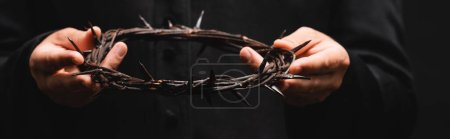 Photo for Horizontal crop of priest holding wreath with spikes isolated on black - Royalty Free Image