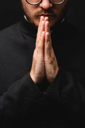 Photo pour Vue partielle du prêtre barbu avec les mains priantes isolées sur noir - image libre de droit