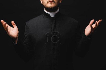 Photo pour Vue recadrée du prêtre avec les mains tendues isolées sur noir - image libre de droit