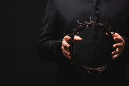Photo for Cropped view of pastor holding wreath with spikes in hands isolated on black - Royalty Free Image