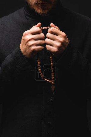 Photo pour Vue recadrée du prêtre tenant des perles de chapelet dans les mains isolées sur noir - image libre de droit