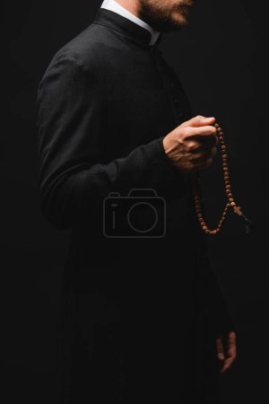 Photo for Cropped view of priest holding rosary beads and standing isolated on black - Royalty Free Image