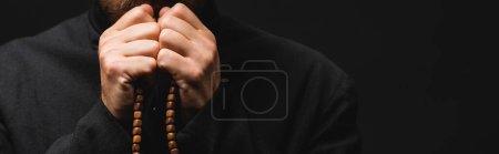 Photo pour Récolte panoramique de prêtre tenant chapelet perles dans les mains isolées sur noir - image libre de droit