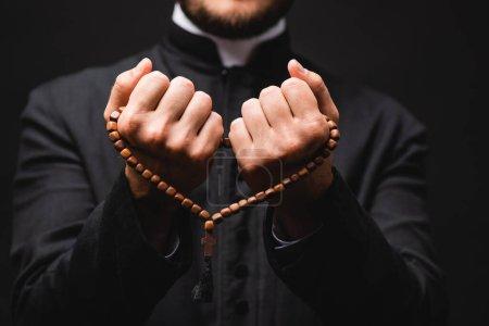 Photo pour Foyer sélectif du pasteur tenant chapelet perles dans les mains et priant isolé sur noir - image libre de droit
