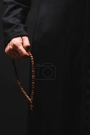Photo pour Vue partielle du pasteur tenant à la main des perles de chapelet isolées sur noir - image libre de droit