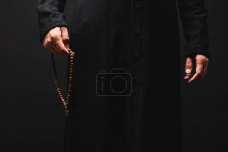 Photo pour Vue partielle du prêtre tenant à la main des perles de chapelet isolées sur noir - image libre de droit