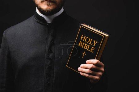 Photo pour Vue recadrée du prêtre tenant la bible sainte isolée sur noir - image libre de droit