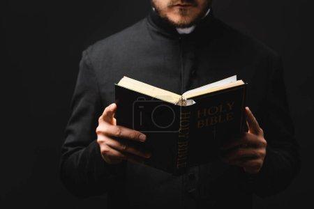 Photo pour Vue partielle du pasteur barbu lisant la bible sainte isolée sur noir - image libre de droit