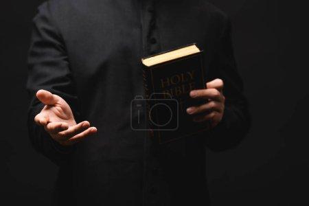 Photo pour Vue partielle du prêtre tenant la bible sainte tout en gesticulant isolé sur noir - image libre de droit