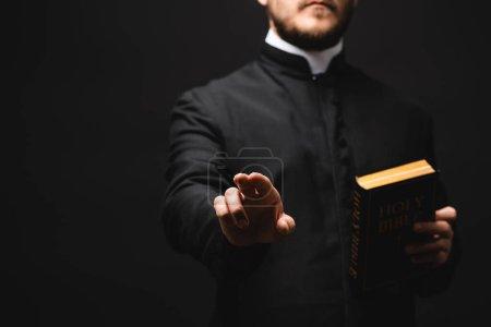 Photo pour Foyer sélectif du prêtre tenant la bible sainte tout en gesticulant isolé sur noir - image libre de droit