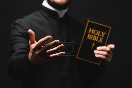 Photo pour Foyer sélectif du pasteur tenant la bible sainte tout en gesticulant isolé sur noir - image libre de droit