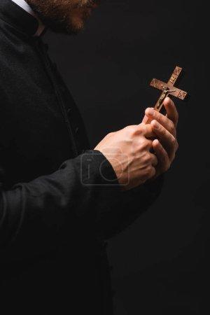 Photo pour Vue recadrée du prêtre tenant la croix en bois isolée sur noir - image libre de droit