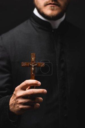 Photo pour Foyer sélectif du prêtre tenant la croix en bois isolé sur noir - image libre de droit