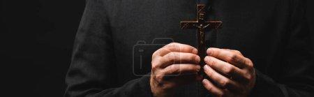 Photo pour Culture panoramique de pasteur tenant croix en bois isolé sur noir - image libre de droit