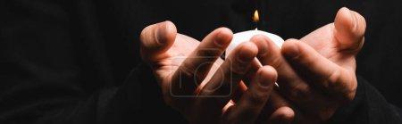 Photo pour Récolte horizontale de prêtre tenant bougie brûlante isolé sur noir - image libre de droit